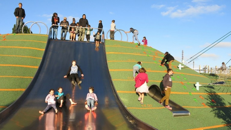 Kids and parents playing on a big slide at the Margaret Mahy playground in Christchurch