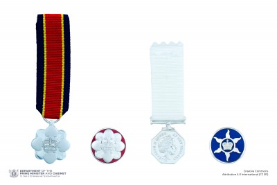Composite image of the miniatures and lapel badges of the New Zealand Antarctic Medal and the New Zealand Distinguished Service Decoration